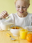 Girl pouring milk over cornflakes