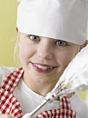 Girl in chef's hat and apron with beater