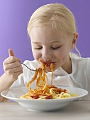A little blonde girl eating spaghetti with tomato sauce