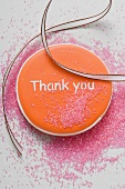 An orange biscuit with the words 'Thank you'