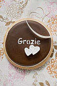 A chocolate biscuit with the word 'Grazie' (close-up)