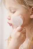 Girl massaging her cheek with exfoliating brush