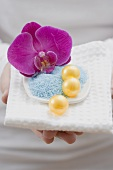 Young woman holding bath salts and bath pearls with orchid