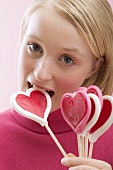 Young woman biting into a heart-shaped lollipop