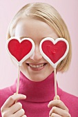 Love is blind: woman with heart-shaped lollipops in front of her eyes