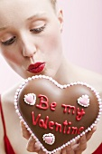 Young woman holding a chocolate heart for Valentine's Day