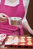 Young woman sprinkling icing sugar over fresh baking