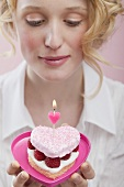 Young woman holding raspberry cake with candle in heart-shaped dish