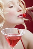 Young woman with Cosmopolitan eating a cherry