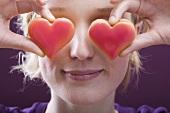 Junge Frau mit zwei Herzkeksen vor den Augen