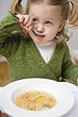 Small girl eating soup with teddy bear pasta