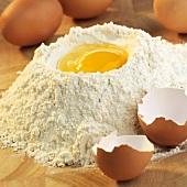 Baking ingredients: egg in well in mound of flour
