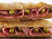 Zwei Baguettesandwiches mit Salami und Oliven