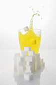 Orangeade with sugar cubes, splashing out of glass