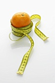 An orange with a tape measure