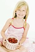 Blond girl holding small basket of fresh raspberries