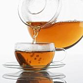 Tee in eine Glastasse eingiessen