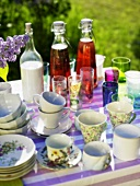 Cups, glasses, drinks & purple lilac on table out of doors