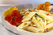 Penne with vegetables and nasturtium flowers