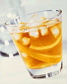 A glass of orange juice with ice cubes and orange slices
