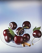 Cherries and cinnamon sticks on glass plate