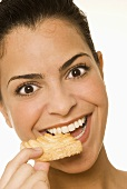 Young woman eating a sweet pastry