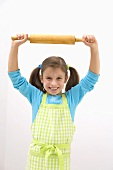 Girl in apron with flour on her face holding rolling pin