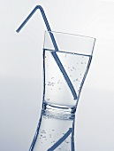 A glass of mineral water with straw
