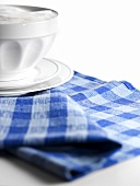Café au lait in bowl on checked cloth