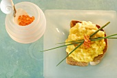 Scrambled egg, salmon caviar and chives on toast