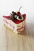 A piece of cherry cheesecake with chocolate shavings