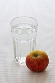 A glass of water and an apple