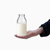 Hand holding a milk bottle