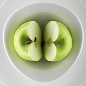 Halved green apple in a bowl