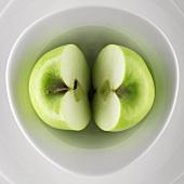 Halbierter grüner Apfel in einer Schale