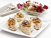 Grilled chicken breasts with slices of lemon and salad