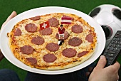 Salami pizza with flags and football figure