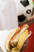 Footballer holding hot dog (sausage & mustard in bread roll)
