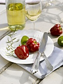 Red and green chillies and silver cutlery on white plate