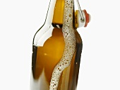 Flip-top bottle with beer frothing out