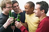 Four men clinking bottles of beer