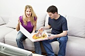 Young couple with pizza sitting in front of TV