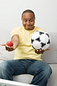 Young man with apple and football watching TV