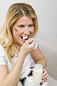 Young woman with football eating natural yoghurt
