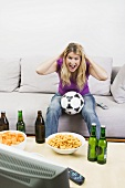 Young woman with football, beer bottles & crisps watching TV