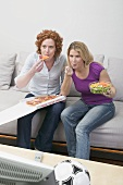 Two friends eating pizza and salad while watching TV