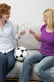 Two friends with sparkling wine and football