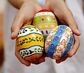 Child's hands holding three Easter eggs