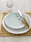 Place-setting with knife and fork on wooden mat, glass