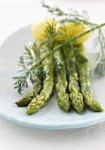 Four spears of green asparagus with potatoes and dill